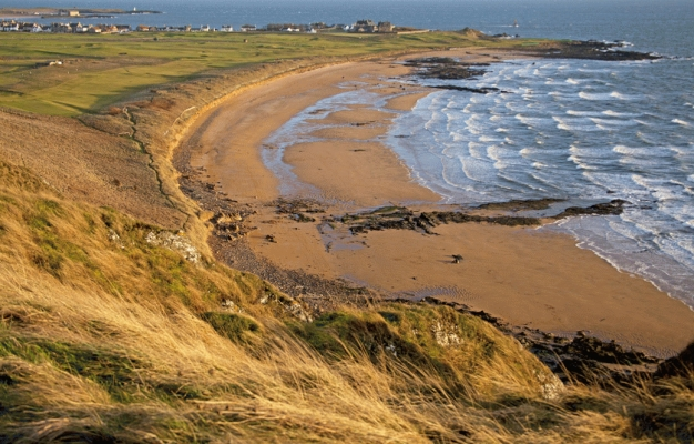 Elie golf course with the firth of forth waves breaking on the beach.