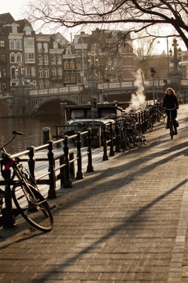 The Netherlands: An early morning cyclist by the river Amstel