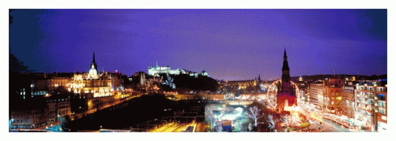 A panoramic view of floodlit Edinburgh Castle and surrounding city..